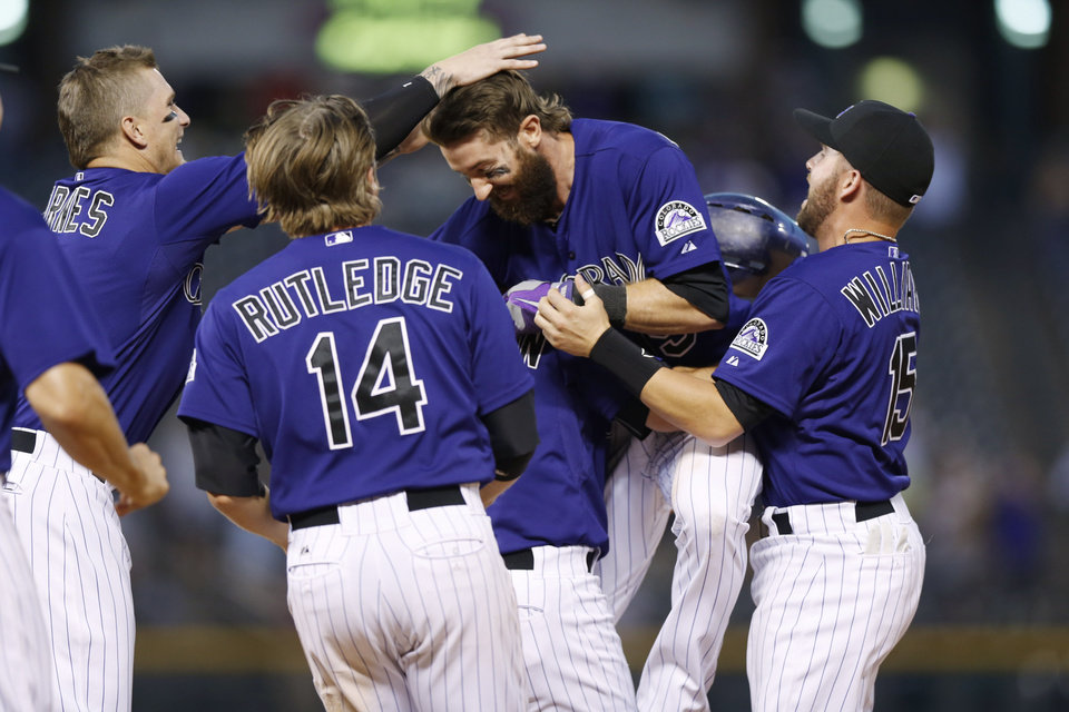 Photo - Colorado Rockies' Charlie Blackmon, second from right, is swarmed by teammates, from left, Brandon Barnes, left, Josh Rutledge (14) and Jackson Williams, right, after Blackmon's walkoff, RBI-single against the San Francisco Giants in the ninth inning of the Rockies' 10-9 victory in a baseball game in Denver on Monday, Sept. 1, 2014.  Rockies Charlie Culberson is obscured between Rutledge and Blackmon. (AP Photo/David Zalubowski)