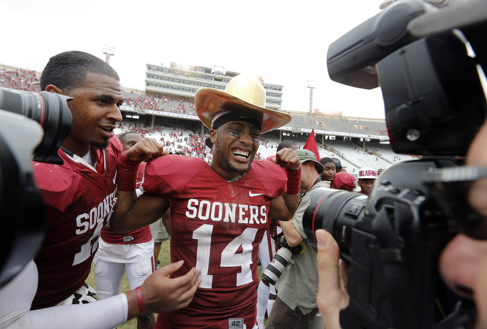 Photo - OU's Aaron Colvin (14) wears the Golden Hat Trophy after the Sooner's 63-21 win over Texas during the Red River Rivalry college football game between the University of Oklahoma (OU) and the University of Texas (UT) at the Cotton Bowl in Dallas, Saturday, Oct. 13, 2012. Photo by Chris Landsberger, The Oklahoman