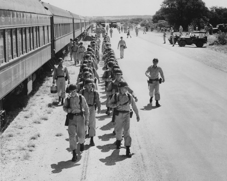 """Photo - Thunderbirds are shown debarking from troop train at Fort Hood.  There'll be a lot of trim waistlines when Oklahoma's Thunderbirds return from two weeks here on this Texas plain.  For 50 weeks of the year, these Oklahoma National guardsmen live the civilian life complete with air conditioning, automobiles and other items that make living easy.   Things Different But the minute the 45th infantry division arrives, that all is passed behind because here one walks where he's going and the only conditioning the air gets is what a hot Texas sun gives it.  The first few days will be used to work up to the second week which will be spent in and out 'of the field' where the big gunnery firing and the infantry tactical problems will be worked out.  As in the past, division surgeons and commanders will keep a close eye on the thermometer because they too, know what it is to step out of air-conditioned offices into the great outdoors in one big jump. Weight to Wane. But by the end of the 2-week field training, these Oklahomans should have left quite a few excess pounds here in Texas and return with a good lone star suntan.  By noon Monday, all units of the division were to be on the post and their members ready to join training which began at 7:30 a.m.  First up to bat on the training schedule was rifle and machine-gun markmanship training and 'on-the-job' work for the division's other specialists. Cooks Are Ready. With the cooks already having finished their school before camp began, four other division schools are scheduled to open as the week rolls around.  Specialty training will be given by engineer demolition experts, signal corps public information and division intelligence before the camp is closed.""""  Photographer unknown.  Published in The Oklahoma City Times 08/08/1955."""