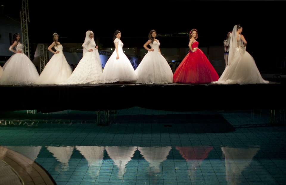 Photo - In this photo taken Friday, May 2, 2014, models display creations by designer Fayzeh Pearl on the catwalk during a fashion show on the second day of Palestine Fashion Week 2014, in the West Bank city of Ramallah. (AP Photo/Nasser Nasser)