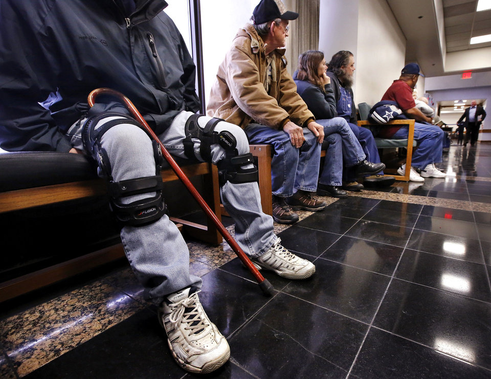 A man with a cane and wearing braces on both knees sits in a hallway with others waiting to be called to meet with an attorney at Workers' Compensation Court in the Denver Davison Building near the state Capitol.