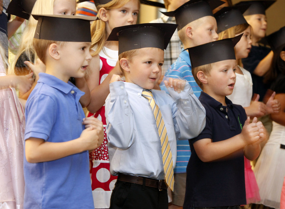 Photo - Christian Holden, left, Will Boyd and Jaxon Hutton sing during teacher Debbie Crouch's kindergarten graduation ceremony at Centennial Elementary School in Edmond.  By Paul Hellstern, The Oklahoman  PAUL HELLSTERN - Oklahoman