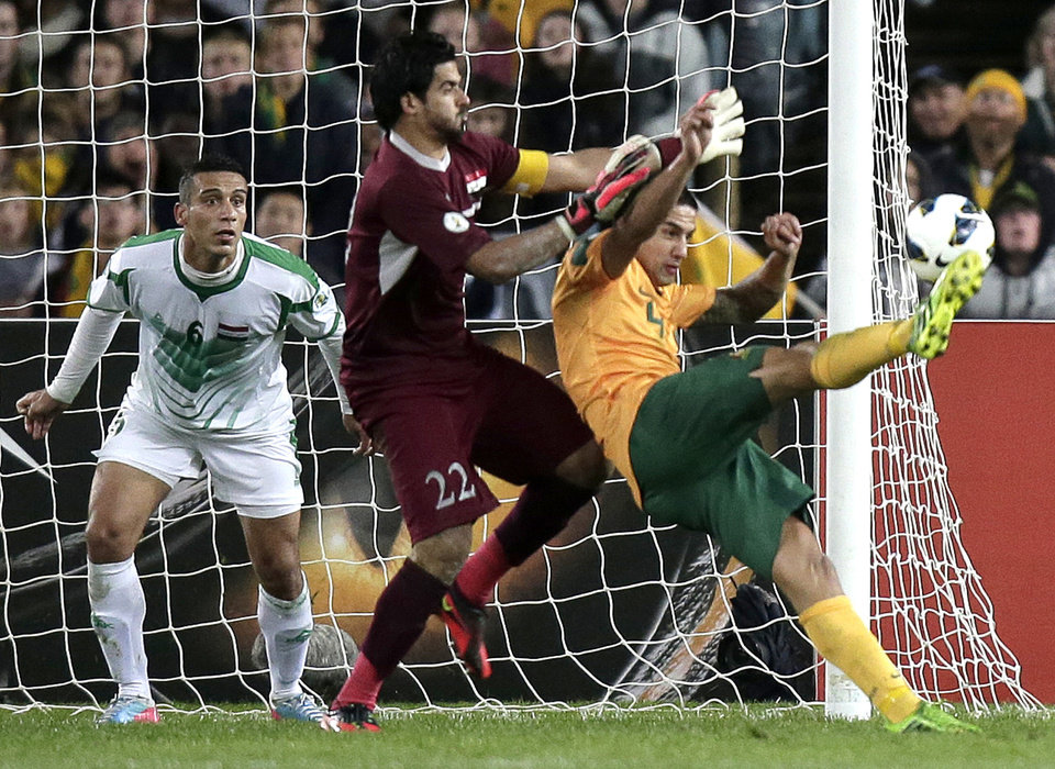 Photo - Australia's Tim Cahill, right, attempts to score on Iraq's Noor Sabri Abbas as Iraq's Aliadnan Kadhim, left, guards the goal during their World Cup soccer Asian qualifying match at the Sydney Olympic Stadium in Sydney, Australia, Tuesday, June 18, 2013. (AP Photo/Rick Rycroft)