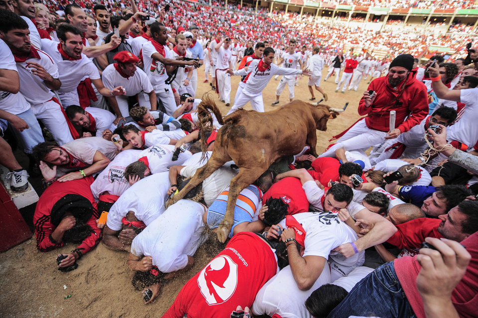 Photo - A cow jumps over revelers who wait for the animal on the bull ring, at the San Fermin festival, in Pamplona, Spain, Tuesday, July 8, 2014. Revelers from around the world in Pamplona take part in an eight-day event of the running of the bulls glorified by Ernest Hemingway's 1926 novel
