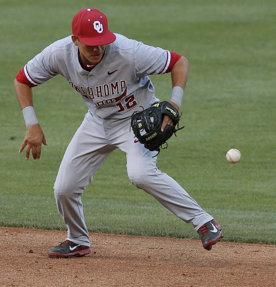 Photo - OU's Hector Lorenzana bobbles the ball in the third inning of a Bedlam baseball game between the University of Oklahoma and Oklahoma State University at Chickasaw Bricktown Ballpark in Oklahoma City, Thursday, May 15, 2014. Photo by Bryan Terry, The Oklahoman
