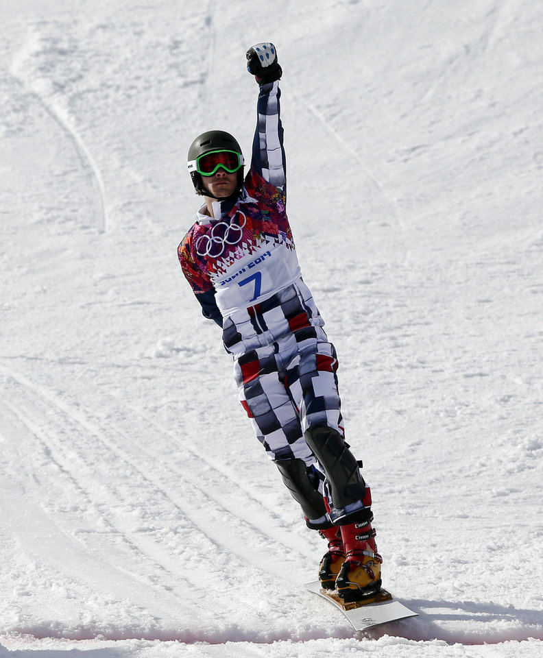 Photo - Russia's Vic Wild celebrates as he crosses the line to win the gold medal in the men's snowboard parallel giant slalom final at the Rosa Khutor Extreme Park, at the 2014 Winter Olympics, Wednesday, Feb. 19, 2014, in Krasnaya Polyana, Russia. (AP Photo/Andy Wong)