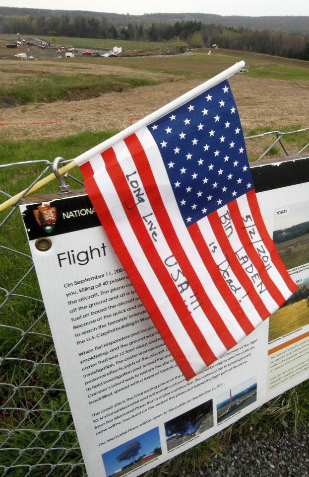 Photo - An American is flag placed at the temporary memorial to United Flight 93 in Shanksville, Pa., with the crash site and permanent memorial construction in the rear on Monday, May 2, 2011. Osama bin Laden, the face of global terrorism and architect of the Sept. 11, 2001, attacks, was killed in a firefight with elite American forces in Pakistan on Monday, May 2, 2011 then quickly buried at sea.  (AP Photo/Gene J. Puskar) ORG XMIT: PAGP102