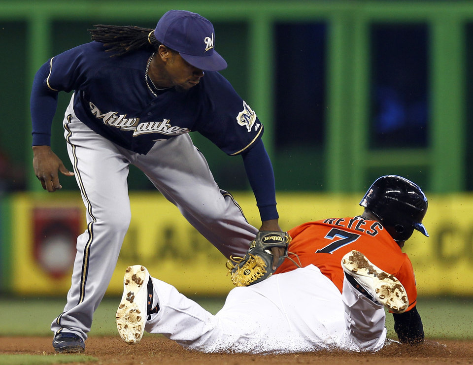 Photo -   Miami Marlins' Jose Reyes steals second on a late throw to Milwuakee Brewers second baseman Rickie Weeks (23) during the first inning of a baseball game in Miami, Monday, Sept. 3, 2012. (AP Photo/J Pat Carter)