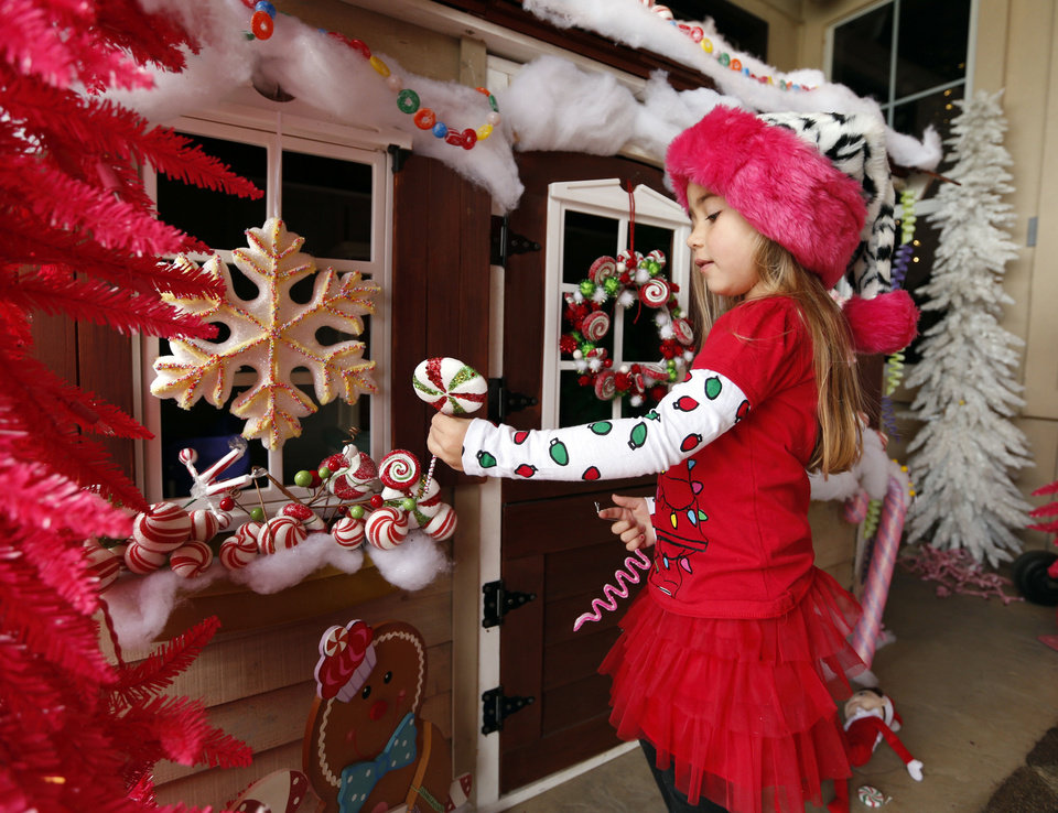 Photo - Mike and Debbie McCurdy's granddaughter Alivia Hutchinson, 4, decorates a playhouse on the back porch of the McCurdy home. PHOTO BY STEVE SISNEY, THE OKLAHOMAN  STEVE SISNEY
