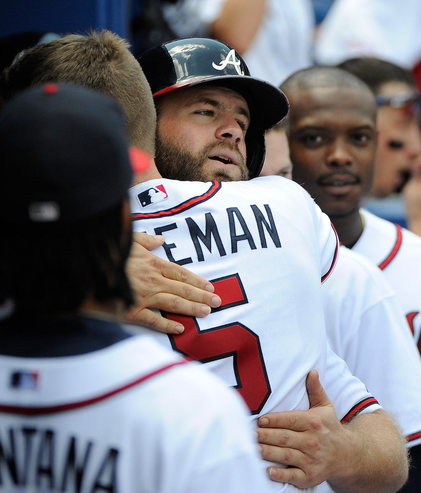 Photo - Atlanta Braves' Evan Gattis, center, is congratulated by teammate Freddie Freeman after his solo home run against the San Diego Padres during the seventh inning of a baseball game Monday, July 28, 2014, in Atlanta. (AP Photo/David Tulis)