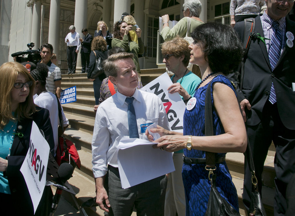 City council candidate Mel Wymore, center, talks with Leah Gunn Barrett, right, New Yorkers Against Gun Violence (NYAGV) executive director, following a gun law rally on Friday, June 14, 2013 on the steps of New York City Hall. If Wymore wins a council seat it would mark the first transgender officeholder for the city. (AP Photo/Bebeto Matthews)