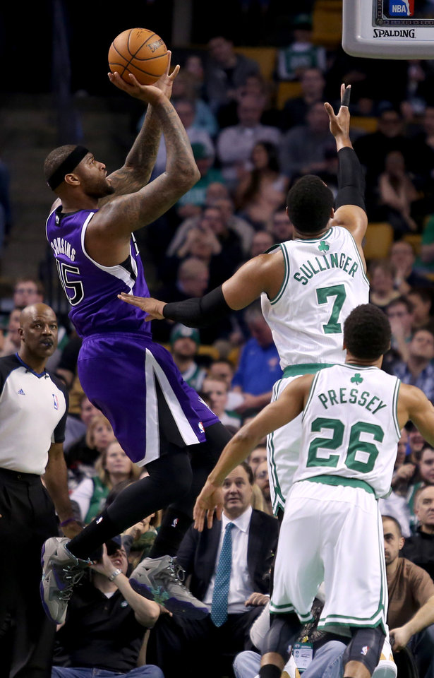 Photo - Sacramento Kings center DeMarcus Cousins (15) shoots against the defense of Boston Celtics center Jared Sullinger (7) as Celtics point guard Phil Pressey (26) looks on during the first half of an NBA basketball game on Friday, Feb. 7, 2014, in Boston. (AP Photo/Mary Schwalm)