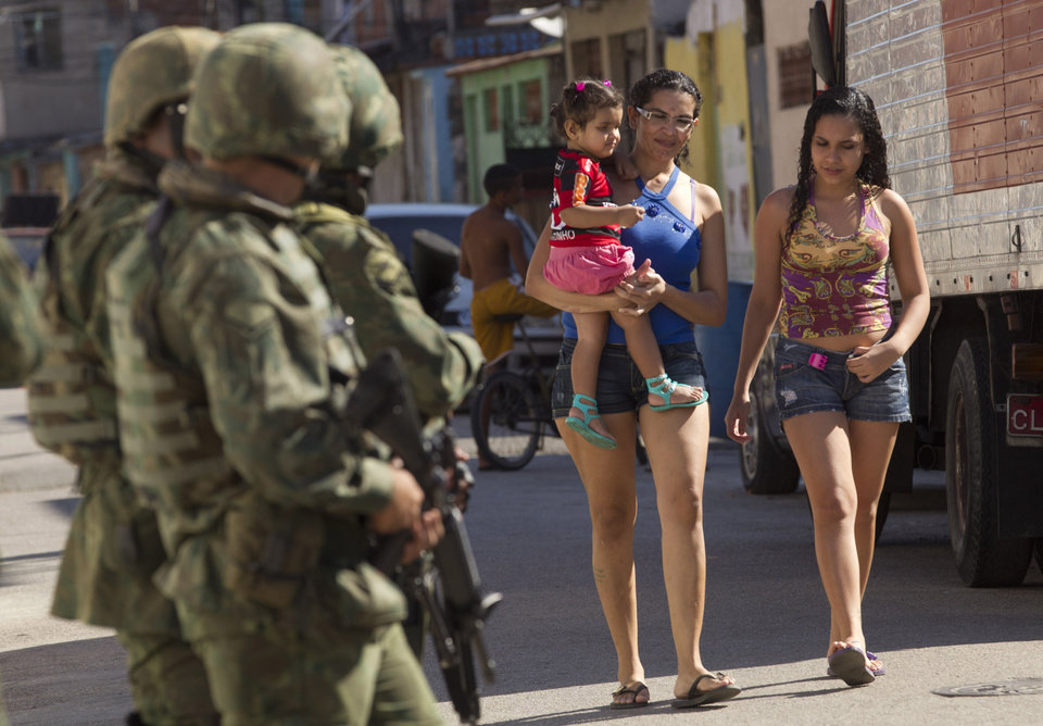 Photo -   In this Oct. 1, 2012 photo, residents walk through the street as soldiers patrol ahead of municipal elections in the Fogo Cruzado slum of Rio de Janeiro, Brazil. Brazil will hold nationwide municipal elections on Sunday, Oct. 7. (AP Photo/Silvia Izquierdo)