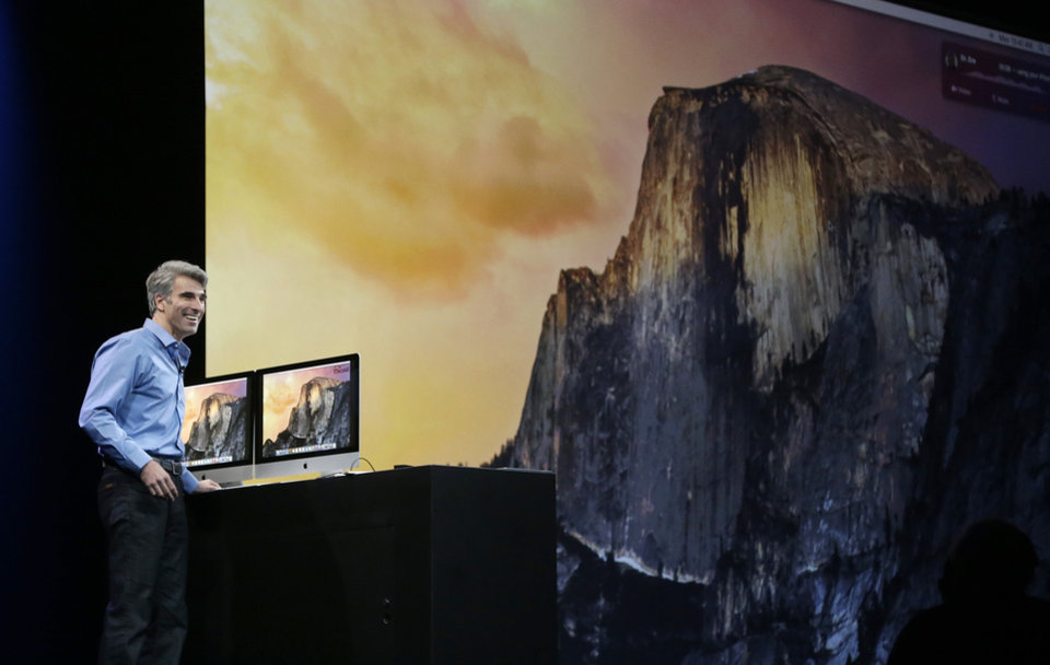 Photo - Apple senior vice president of Software Engineering Craig Federighi speaks in front of a screen for the Yosemite operating system at the Apple Worldwide Developers Conference in San Francisco, Monday, June 2, 2014. (AP Photo/Jeff Chiu)