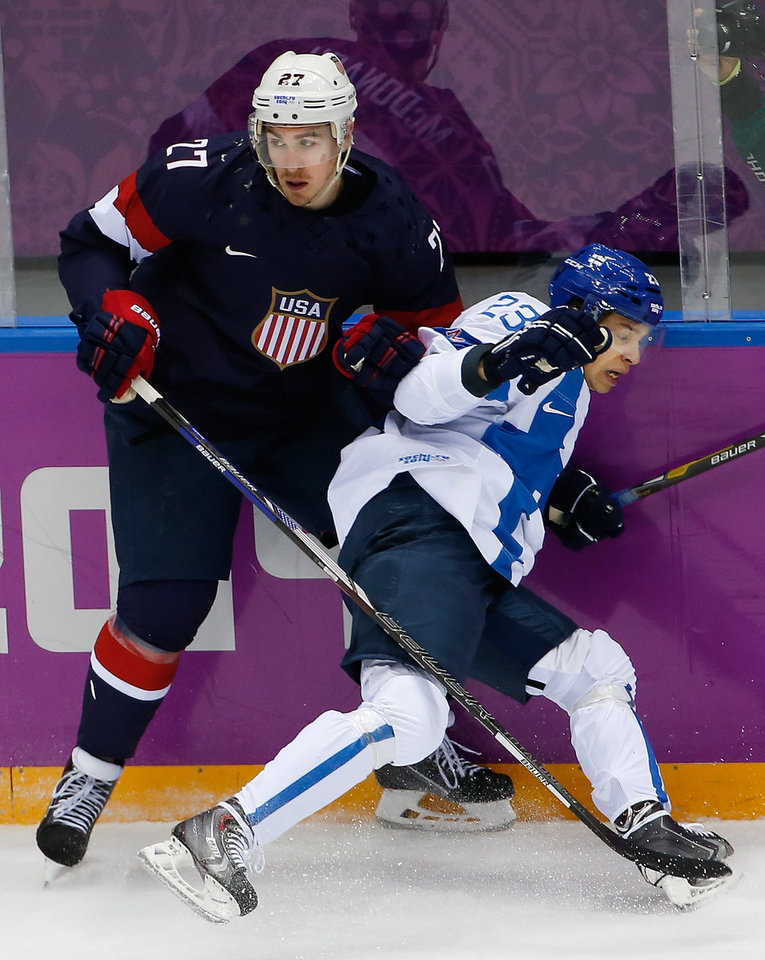 Photo - Ryan McDonagh of the United States battles with Sakari Salminen of Finland against the boards during the first period of the men's bronze medal ice hockey game at the 2014 Winter Olympics, Saturday, Feb. 22, 2014, in Sochi, Russia. (AP Photo/Julio Cortez)