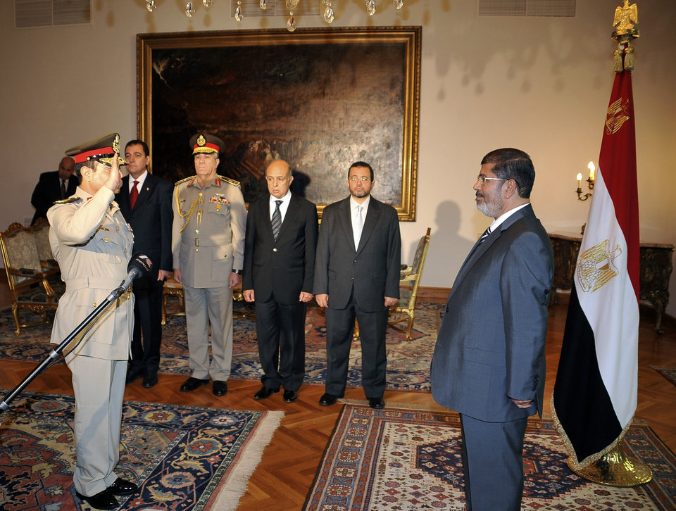 Photo -   RETRANSMISSION FOR ALTERNATIVE CROP - Egyptian President Mohammed Morsi, right, swears in newly-appointed Minister of Defense, Lt. Gen. Abdel-Fattah el-Sissi, left, in Cairo, Egypt, Sunday, Aug. 12, 2012. Egypt's Islamist president ordered his former defense minister and chief of staff to retire on Sunday and canceled the military-declared constitutional amendments that gave top generals wide powers. (AP Photo/Egyptian Presidency)