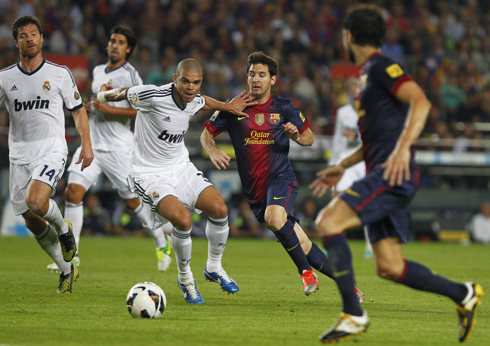 Real Madrid's Pepe from Portugal, centre left, in action with FC Barcelona's Lionel Messi from Argentina, centre right, during a Spanish La Liga soccer match at the Camp Nou stadium in Barcelona, Spain, Sunday, Oct. 7, 2012. (AP Photo/Andres Kudacki)