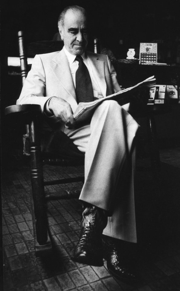 Cattlemen's Cafe owner Gene Wade paused to read the morning newspaper in 1979 in his father's favorite chair.  OKLAHOMAN ARCHIVE PHOTO <strong>Bob Grier - Staff Photo</strong>