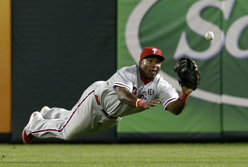 Photo - Philadelphia Phillies right fielder Marlon Byrd lays out for a fly out by Texas Rangers' Donnie Murphy in the sixth inning of a baseball game, Tuesday, April 1, 2014, in Arlington, Texas. Mitch Moreland was out at first trying to get back after heading to second on the play. The Rangers won 3-2. (AP Photo/Tony Gutierrez)