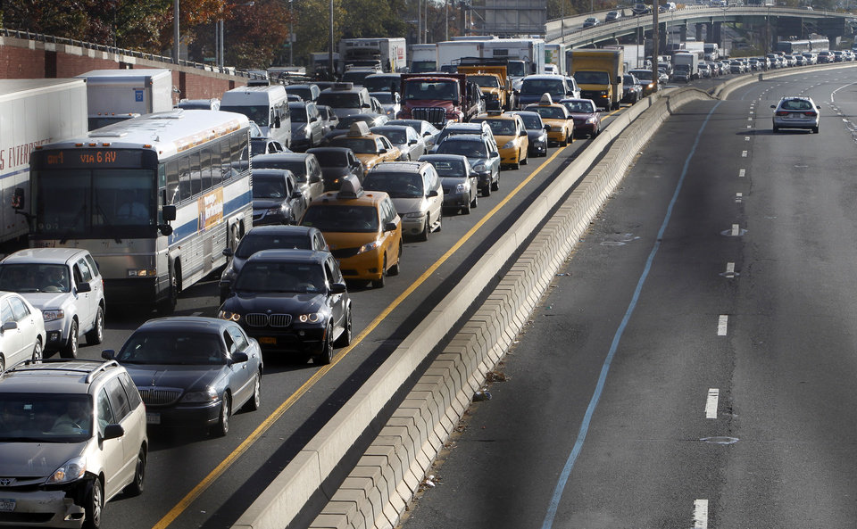 Photo - In a photo made through a chain-link fence, traffic is gridlocked on the Long Island Expressway into Manhattan near the turn off for the Queensboro Bridge, Thursday, Nov. 1, 2012, in the Queens borough of New York. New York's subway system rumbled partially back to life Thursday, though the morning commute was plagued by long delays and massive gridlock on the main highways and bridges leading into the city. (AP Photo/Jason DeCrow) ORG XMIT: NYJD109