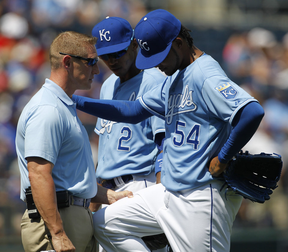 Photo - Kansas City Royals shortstop Alcides Escobar (2) looks on as Kansas City Royals pitcher, Ervin Santana (54) is checked out by trainer, Nick Kenney, after getting hit by a line drive from Washington Nationals batter, Denard Span, in the third inning of a baseball game at Kauffman Stadium in Kansas City, Mo., Sunday, Aug. 25, 2013. (AP Photo/Colin E. Braley)