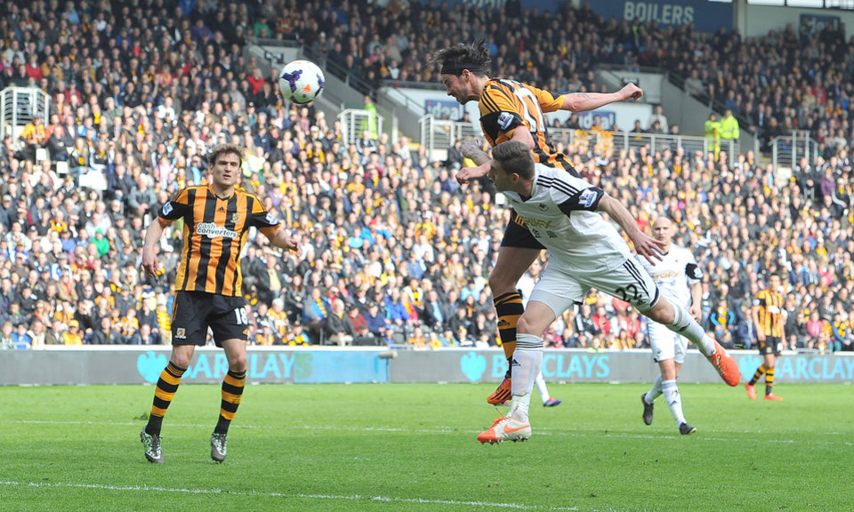 Photo - Hull City's George Boyd, top, heads the ball to score his side's first goal during their English Premier League soccer match against Swansea City at the KC Stadium, Hull, England, Saturday, April 5, 2014. (AP Photo/Dave Howarth, PA Wire)  UNITED KINGDOM OUT    -   NO SALES   -   NO ARCHIVES
