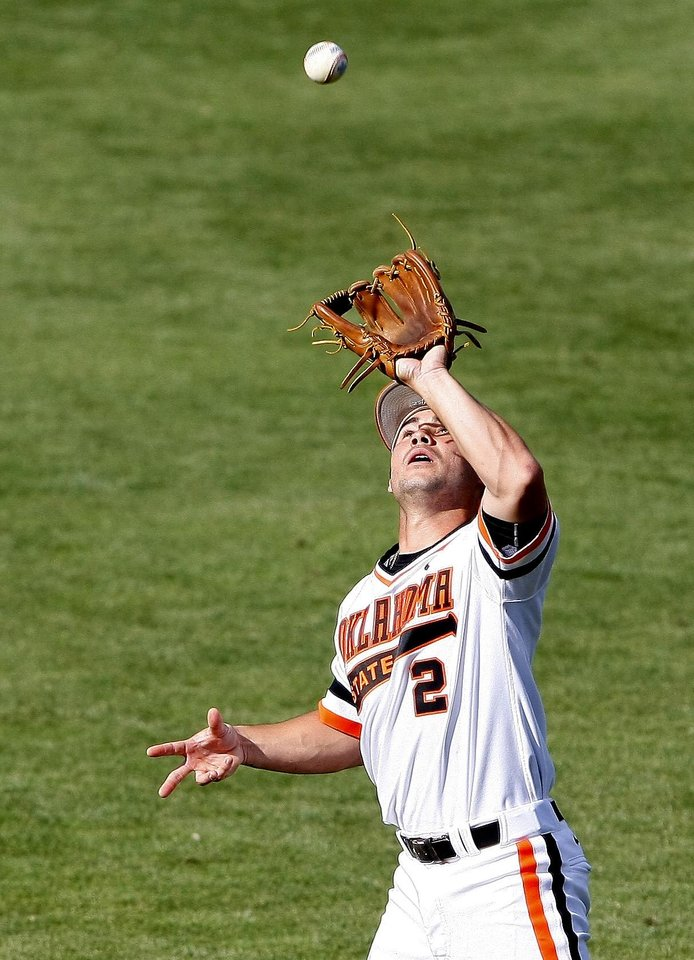 Photo - Oklahoma State second baseman Tim Arakawa catches an Oklahoma fly ball in the bottom of the second inning of a first-round game of the State Big 12 conference NCAA college baseball tournament in Oklahoma City, Wednesday, May 21, 2014. (AP Photo/Alonzo Adams)