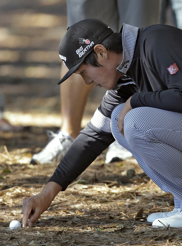 Photo - Danny Lee, of New Zealand, clears debris from around his golf ball after hitting into the trees along the 16th fairway during the first round of the Valspar Championship golf tournament at Innisbrook, Thursday, March 13, 2014, in Palm Harbor, Fla. (AP Photo/Chris O'Meara)