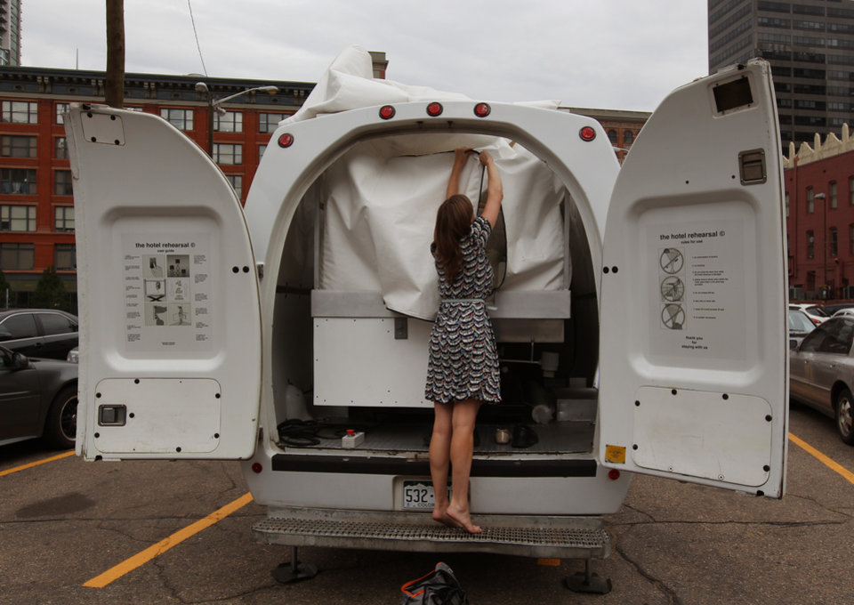 Photo - Amelia Langer, an assistant curator of Draft Urbanism, the art exhibition of the 2013 Biennial of the Americas, unzips the opening to a hotel room made of aluminum and inflated vinyl capable of being held aloft by a van-mounted scissor lift, on promotional display in a parking lot in downtown Denver, Wednesday July 25, 2013. Architectural artist Alex Schweder created the 5 by 7 foot room atop a van for the Biennial in Denver. For $50,000, a guest would get one weekend night in the puffy space, plus lots of extras including a diamond pendant and earring set, two iPod Nanos and a dance party for 100 people in a ballroom of The Curtis Hotel. (AP Photo/Brennan Linsley)