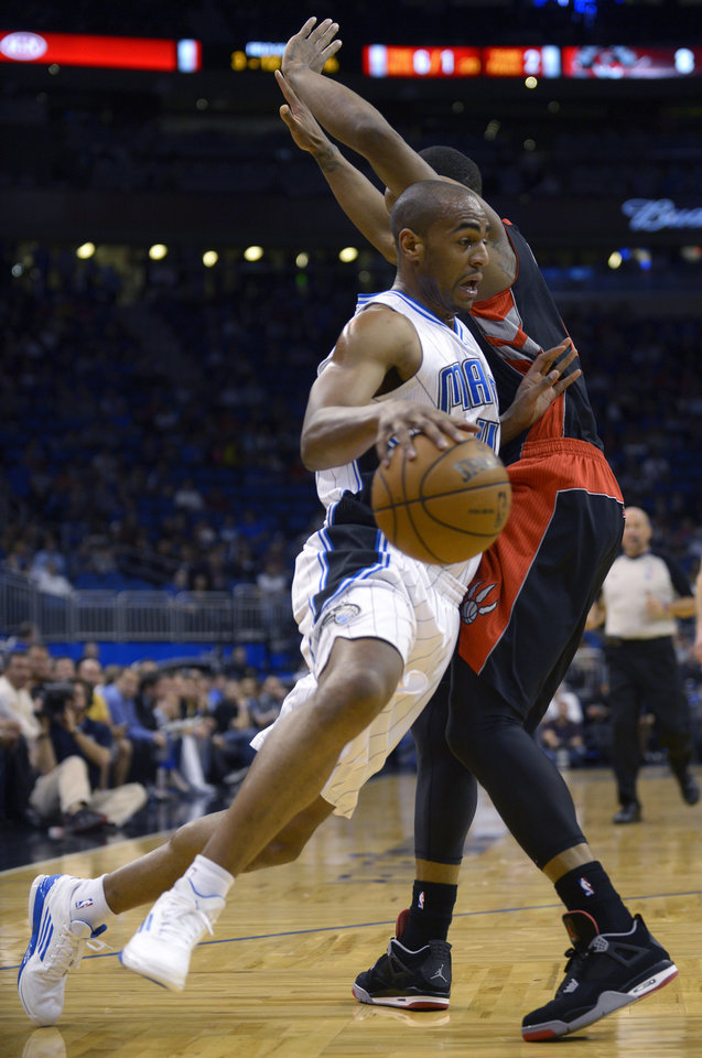 Orlando Magic guard Arron Afflalo, left, drives past Toronto Raptors guard DeMar DeRozan during the first half of an NBA basketball game in Orlando, Fla., Thursday, Jan. 24, 2013.(AP Photo/Phelan M. Ebenhack)