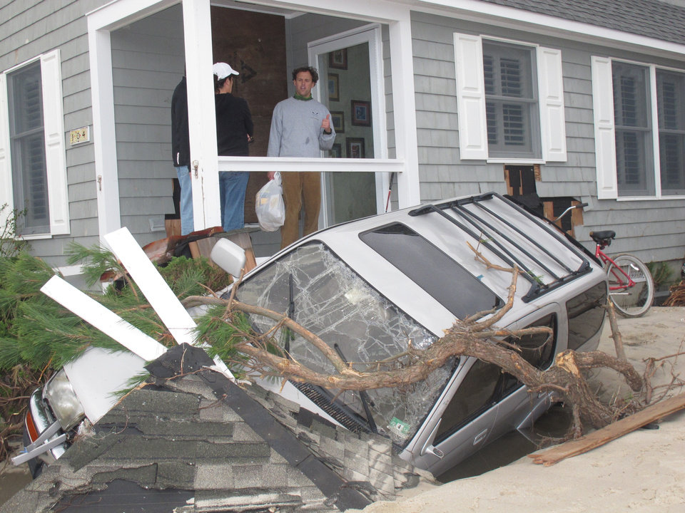 In an Oct. 31, 2012 photo, homeowners in Mantoloking N.J. look at a car that was wrecked by Superstorm Sandy. Even with federal reimbursement for much of the cleanup and rebuilding expenses, hard-hit towns could be facing property tax hikes next year as a result of the unexpected costs, and the loss of millions of dollars of taxable property. (AP Photo/Wayne Parry)