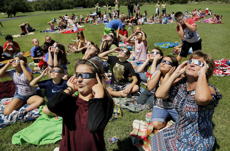 Photo - Kelli Hosford, far right, principal of James Griffith Intermediate School, sits among her students as they gaze upward to watch the eclipse. The entire student body, faculty and some parents gathered in a field on the north side of  JGI to view the solar eclipse Monday afternoon, Aug. 21, 2017.  Special glasses with very dark lenses were purchased to allow teachers and students to safely view the celestial event. Children were served  Moon Pies as a snack to enjoy while viewing the eclipse. Photo by Jim Beckel, The Oklahoman
