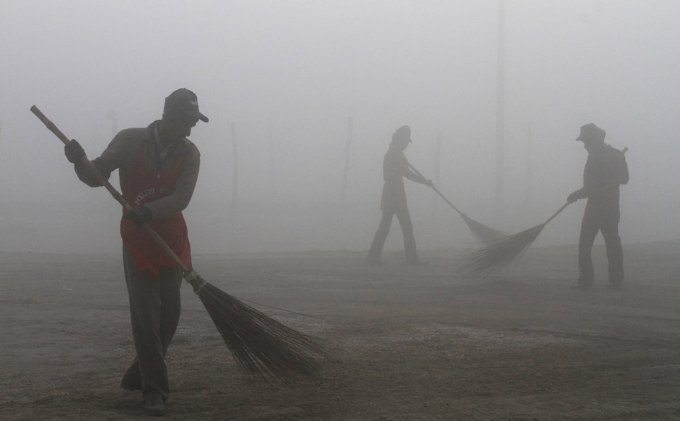 Indian workers sweep the Sangam area on the banks of the Ganges River on a cold and foggy morning in Allahabad, India, Sunday, Dec. 30, 2012. North India continues to face extreme weather conditions with dense fog affecting flights and trains. (AP Photo/Rajesh Kumar Singh)