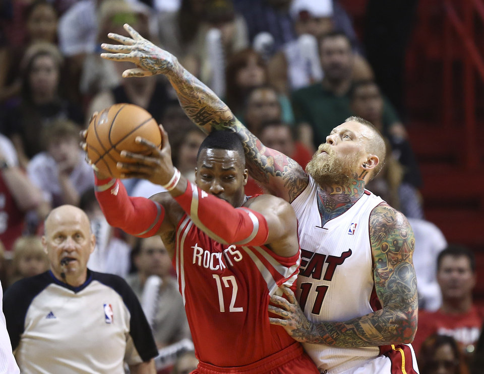 Photo - Miami Heat's Chris Andersen (11) reaches over Houston Rockets' Dwight Howard (12) as he tries to steal the ball during the first half of an NBA  basketball game in Miami, Sunday, March 16, 2014. (AP Photo/J Pat Carter)