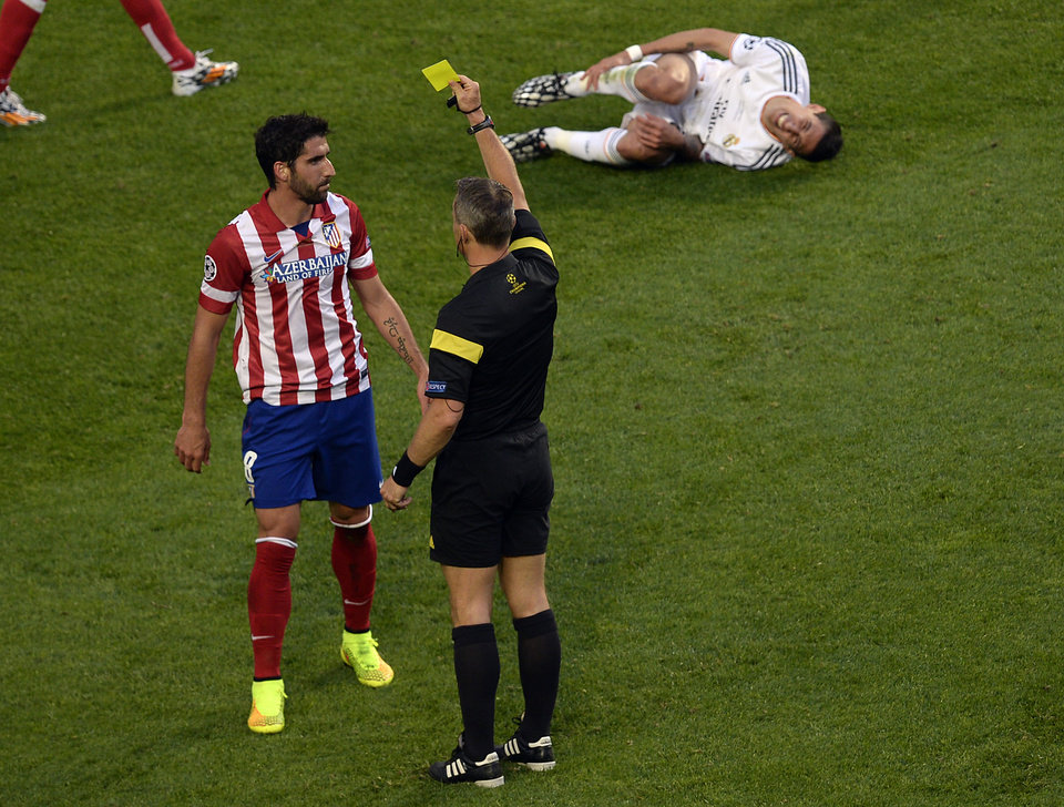 Photo - Atletico's Raul Garcia, left, gets the yellow card by referee Bjorn Kuipers during the Champions League final soccer match between Atletico Madrid and Real Madrid in Lisbon, Portugal, Saturday, May 24, 2014. (AP Photo/Paulo Duarte)