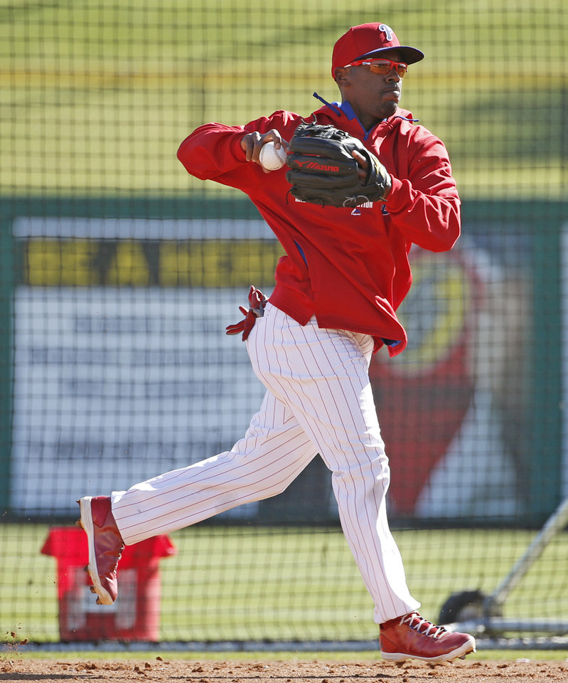 Photo - Philadelphia Phillies shortstop Jimmy Rollins throws to first while fielding balls during batting practice before a spring exhibition baseball game against the New York Yankees,  in Clearwater, Fla., Thursday, March 13, 2014. Rollins was out of the starting lineup Yankees, benched for a third straight game. Rollins said he's healthy and unsure why manager Ryne Sandberg decided to bench him this week. (AP Photo/Kathy Willens, File)
