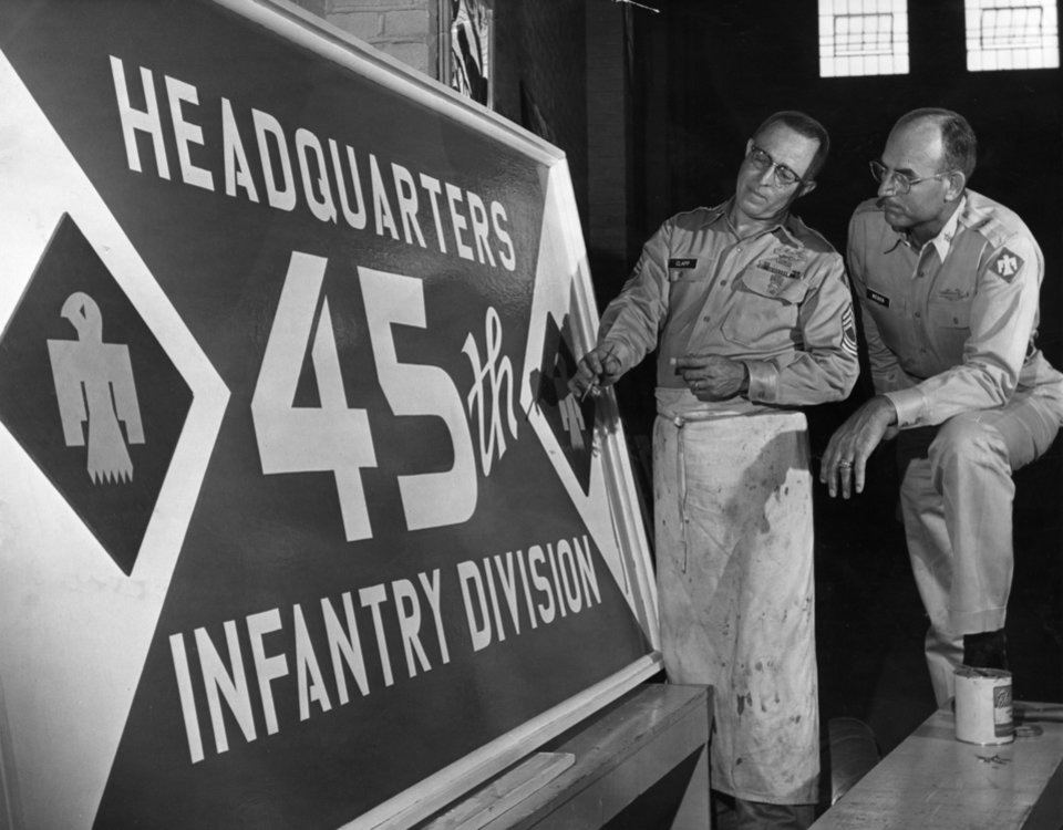 Photo - SIGN OF THE TIMES, summer camp time that is, nears completion at General McLain armory.  Sgt. Jack Clapp, left, and Lt. Col. LaVern Weber inspect the big, blue sign that will greet Thunderbirds of the 45th Infantry Division, Oklahoma National Guard, when they arrive at North Fort Polk, La., Sunday for their annual summer encampment.  Staff photo by Joe Miller.  Staff photo dated 07/09/1962 and published on 07/10/1962 in The Daily Oklahoman.