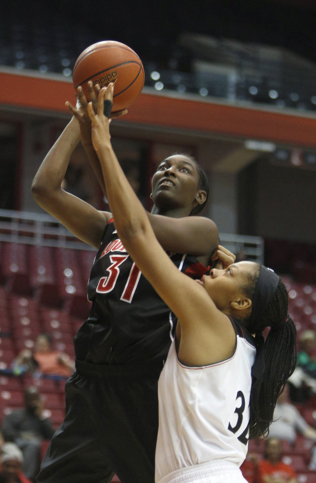 Photo - Louisville forward Asia Taylor (31) looks to shoot against Cincinnati forward Shelbi Chandler (32) during the first half of an NCAA  college basketball game, Saturday, March 1, 2014, in Cincinnati. (AP Photo/David Kohl)