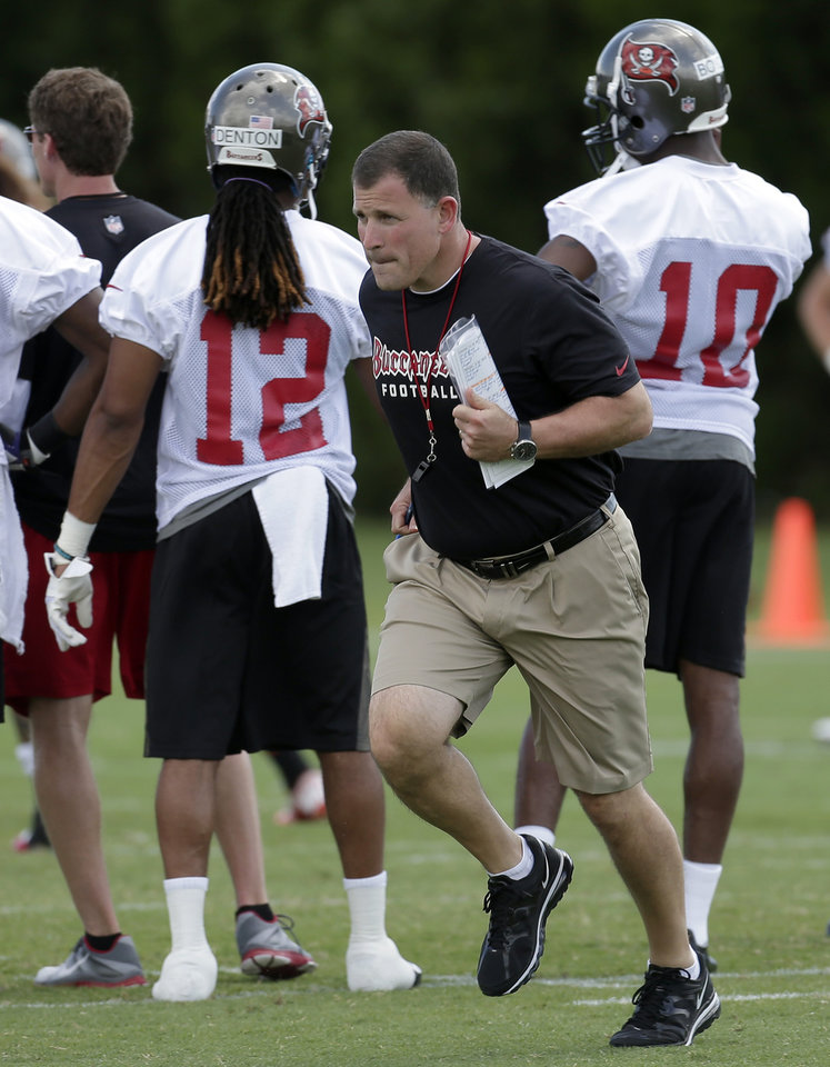 Photo - Tampa Bay Buccaneers head coach Greg Schiano runs across the field during NFL football rookie minicamp Friday, May 3, 2013, in Tampa, Fla. (AP Photo/Chris O'Meara)