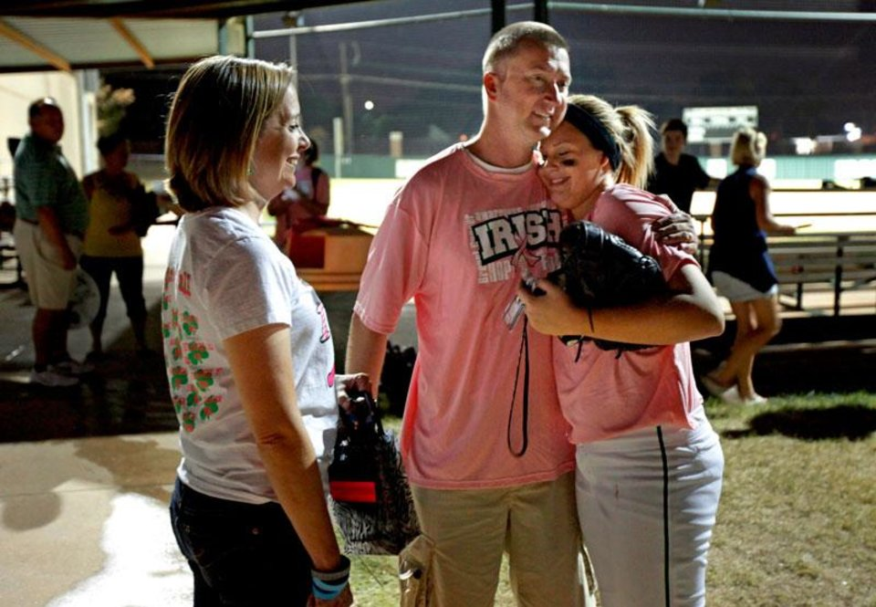 Photo -  Volunteer coach Matt Allen hugs Nicole Frazier as his wife Kelley watches following a Bishop McGuinness softball game in Oklahoma City, Tuesday, Sept. 14, 2011. Allen was diagnosed with brain cancer two years ago and continues his volunteer coaching duties with the softball team. Win-Win Week is a statewide effort by Oklahoma high schools to support cancer awareness.