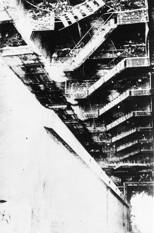 Photo - FILE - This is a 1911 file photo of the collapsed remains of the fire escape of the Triangle Shirt Waist Company in New York City. One hundred years ago, horrified onlookers watched as workers leapt to their deaths from the raging fire in the garment factory. The fire killed 146 workers, mainly young immigrant women and girls, and became a touchstone for the organized labor movement, spurred fire-safety laws and shed light on the lives of immigrant workers. (AP Photo/File)