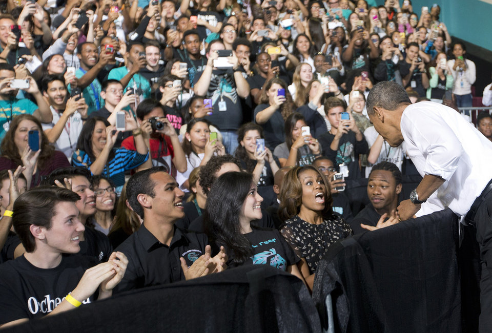 Photo - President Barack Obama reaches over to greet first lady Michelle Obama, who was sitting in the audience with students in the gym at Coral Reef High School, Friday, March 7, 2014, in Miami. Obama traveled to the Miami school to unveil a new initiative to ensure more students complete the Free Application for Federal Student Aid (FAFSA), a document required for most types of school financial aid such as Pell grants. (AP Photo/Pablo Martinez Monsivais)