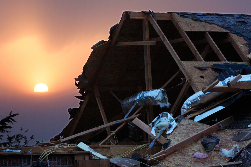A colorful sun sets behind a damaged roof of a home behind the Cedar Valley East Golf Course near Guthrie after a tornado came through the area Tuesday afternoon. Photo by Jim Beckel, The Oklahoman