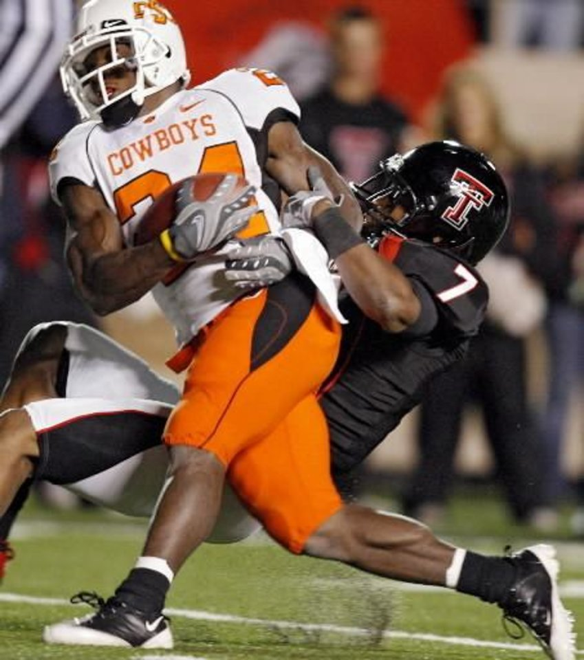 Oklahoma State's Kendall Hunter (24) drags  Texas  Tech's Darcel McBath (7) into the end zone for a touchdown during the first half of the college football game between the Oklahoma State University Cowboys ( OSU) and the  Texas  Tech Red Raiders at Jones AT