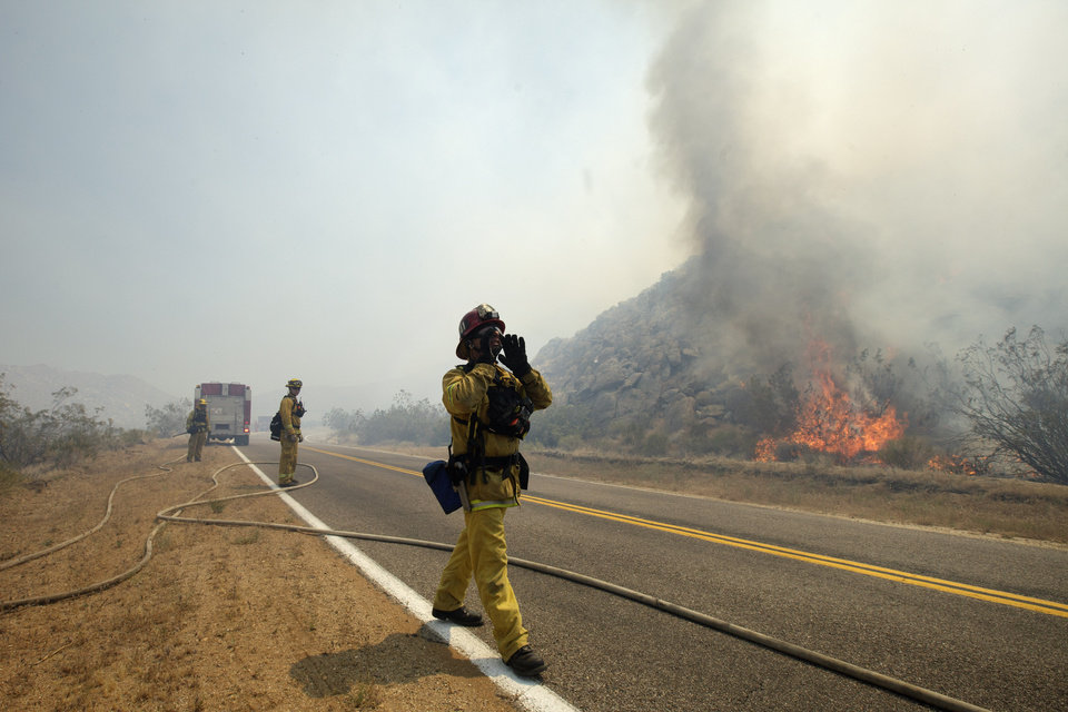 Photo -   Firefighter Jay Dimoff, of the San Bernardino County Fire Department, yells to his crew as they try to keep fire from crossing a San Diego County road Friday, May 25, 2012, near Julian, Calif. The blaze broke out Thursday afternoon east of Julian near Banner Grade. About 100 homes were temporarily evacuated in the Shelter Valley area along Highway 78 during the early stages of the fire but that order was lifted late Thursday. (AP Photo/Gregory Bull)