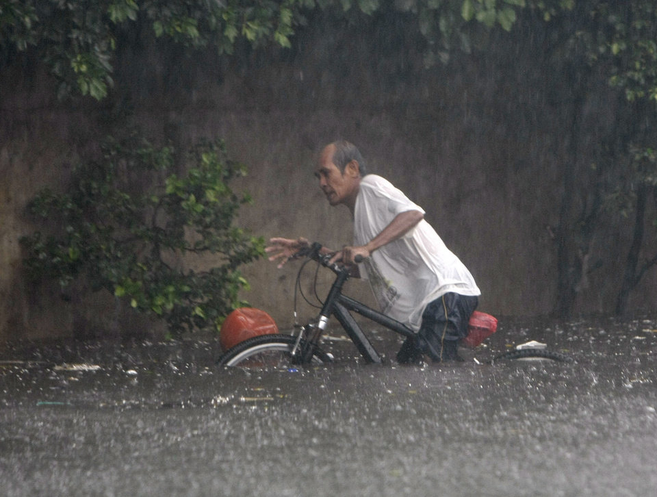 Photo -   A man retrieves a basketball floating on a flooded street following heavy monsoon rains spawned by a tropical depression at suburban Quezon city northeast of Manila, Philippines, Saturday July 21, 2012. The heavy rains flooded most parts of metropolitan Manila Saturday forcing cancellation of classes that created massive traffic jams and closure of business. (AP Photo/Bullit Marquez)