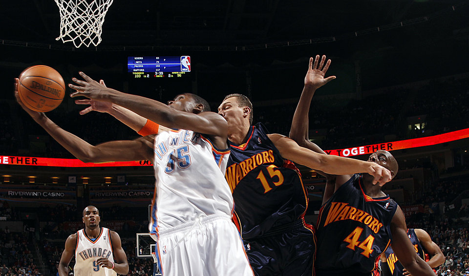 Photo - Oklahoma City's Kevin Durant (35) shoots a lay up as Golden State's Adris Biedrins (15) and Anthony Toliver (44) defend during the NBA game between the Oklahoma City Thunder and Golden State Warriors, Sunday, Jan. 31, 2010, at the Ford Center in Oklahoma City. Photo by Sarah Phipps, The Oklahoman