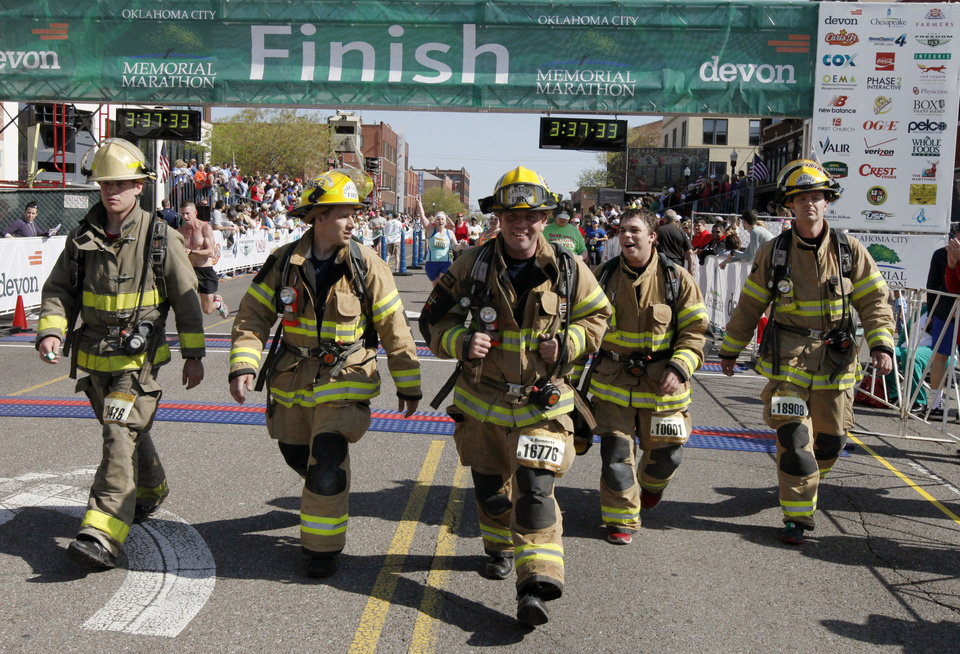 Firefighters in more than sixty pounds of gear cross the half-marathon finish line during the Oklahoma City Memorial Marathon in Oklahoma City, Sunday, April 28, 2013,  By Paul Hellstern, The Oklahoman
