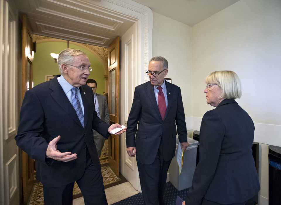 Photo - From left, Senate Majority Leader Harry Reid, D-Nev., Sen. Chuck Schumer, D-N.Y., the Democratic Policy Committee chairman, and Budget Committee Chair Patty Murray, D-Wash., speak privately before attending a news conference on Capitol Hill in Washington, Thursday, Sept. 19, 2013. The Democratic leaders repeated their resolve to not touch the Affordable Care Act if House Republicans make rescinding