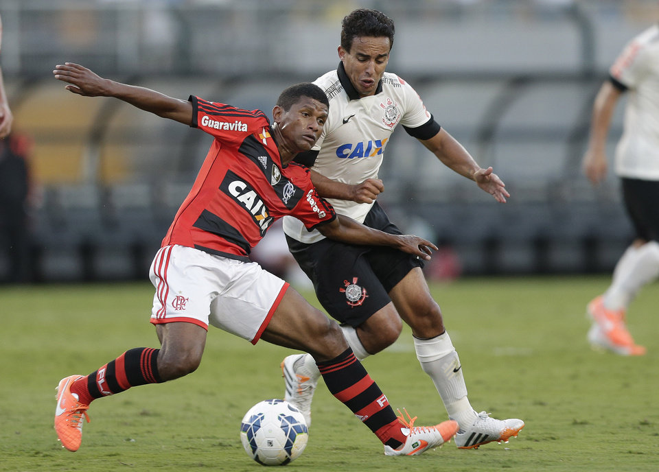 Photo - Flamengo's Marcio Araujo, left, fights for a ball with Corinthians' Jadson during a Brazilian soccer league match in Sao Paulo, Brazil, Sunday, April 27, 2014. (AP Photo/Andre Penner)